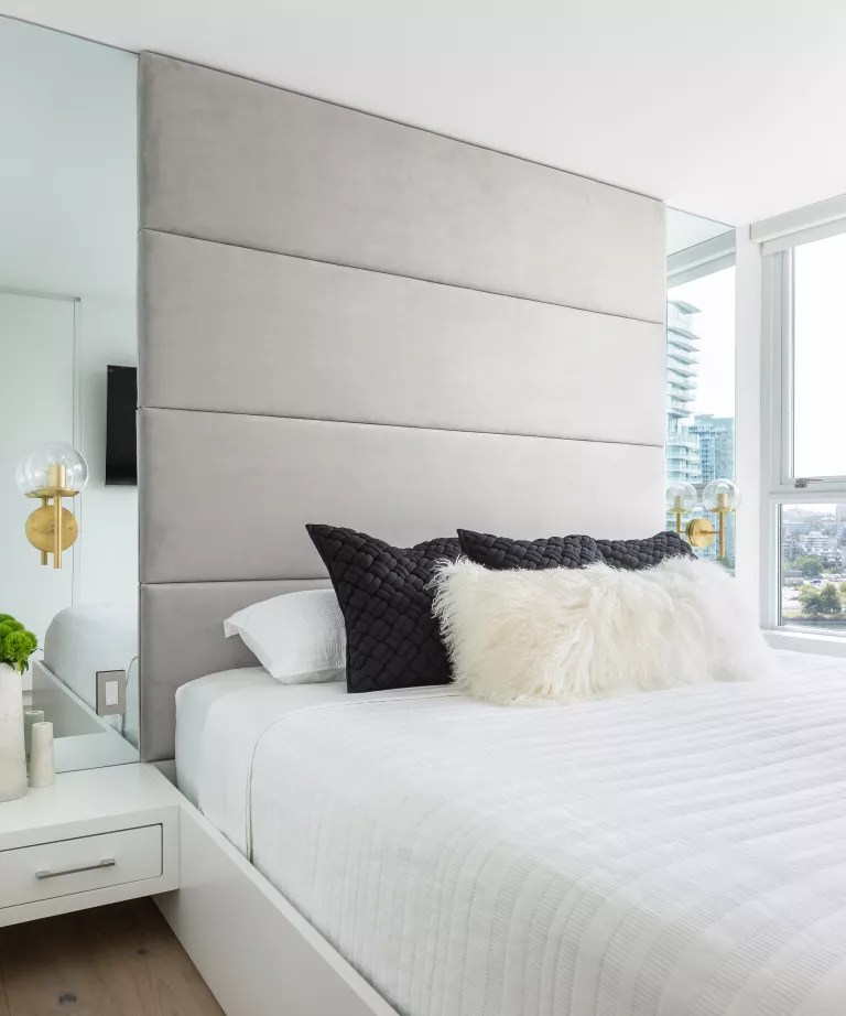 An apartment bedroom with mirrored panels on either side of the bed, reflecting the window view