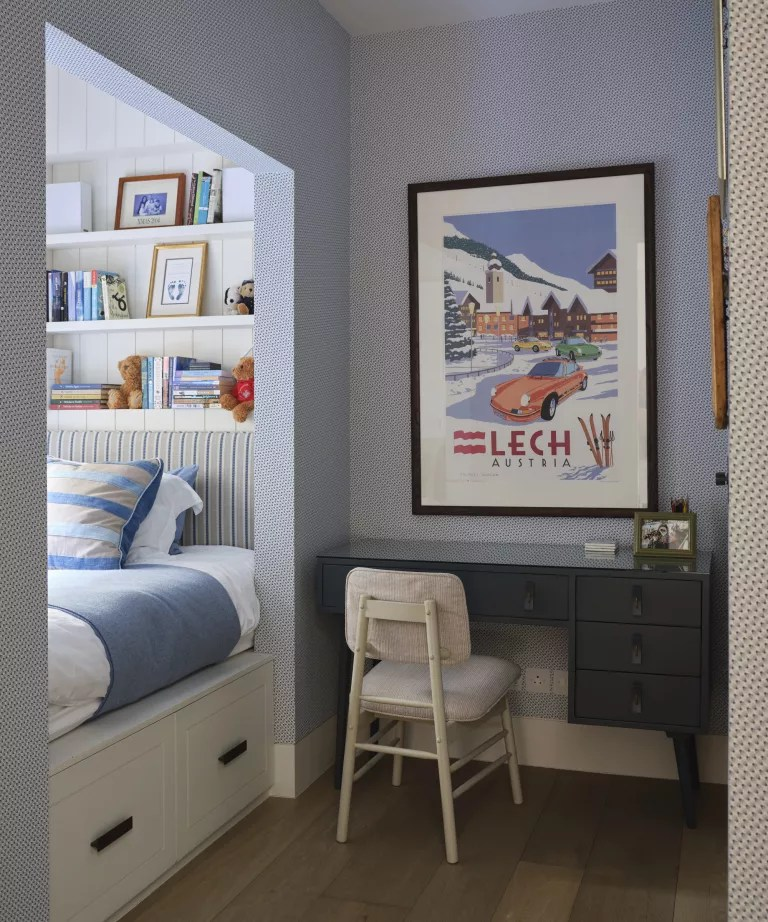 A kids bedroom with blue walls and cubby hole bed with under-bed drawers