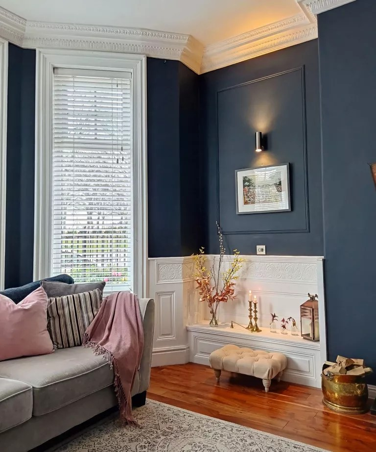 Corner of living room with pink armchair navy blue walls and part of a bay window