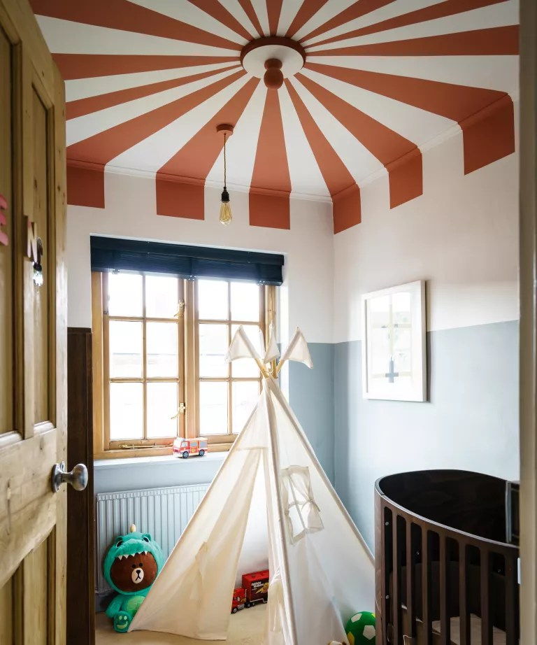 A child's bedroom with a feature ceiling painted in red and white to look like a circus tent