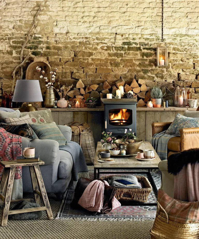 Fall mantel ideas with an exposed stone wall, stove, grey sofas with blankets and firewood and mismatched ornaments on the mantel