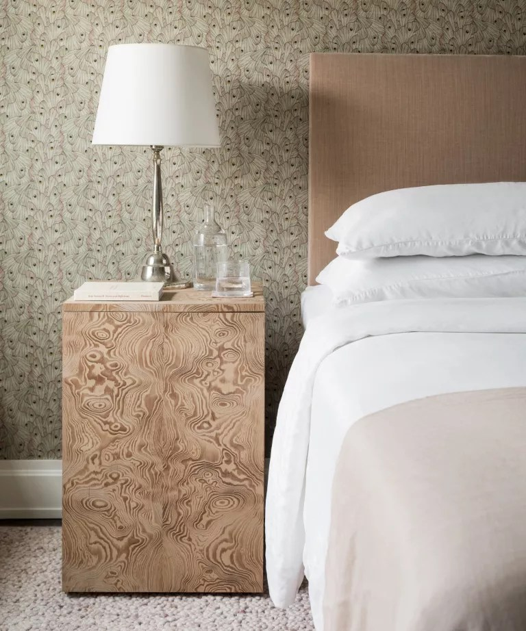 A bedroom with a wooden side table, white lamp, neutral wallpapered walls and a pink textured carpet
