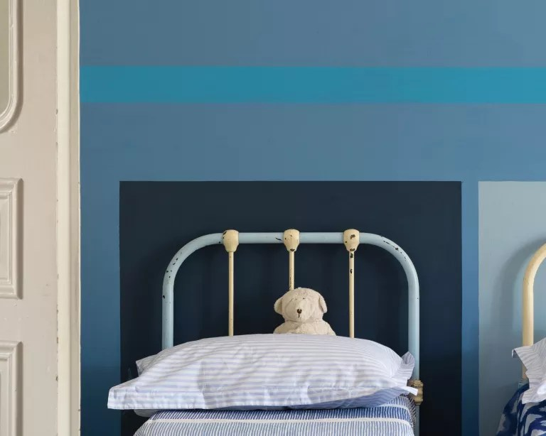 A kids' bedroom with twin beds and blue walls painted in a graphic design in differing tones