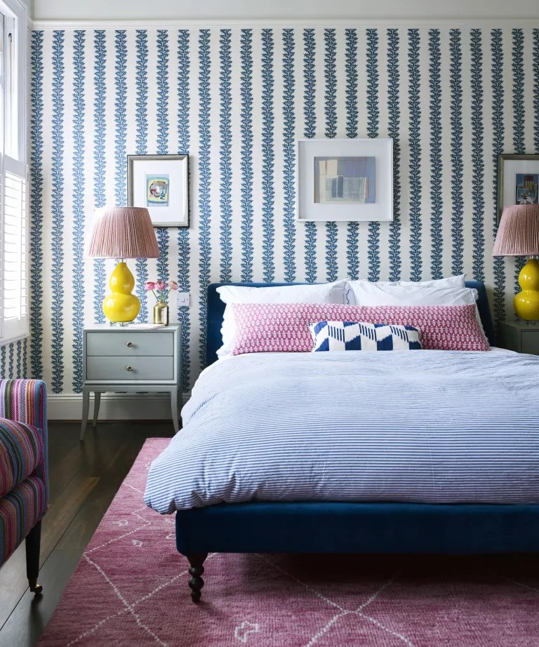 A bedroom with blue striped wallpaper, pink rug and yellow lamps