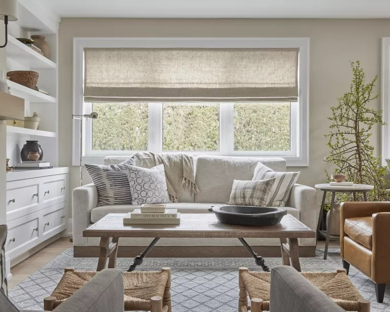 A living room with grey sofa, wooden table, beige walls and warm neutral accessories
