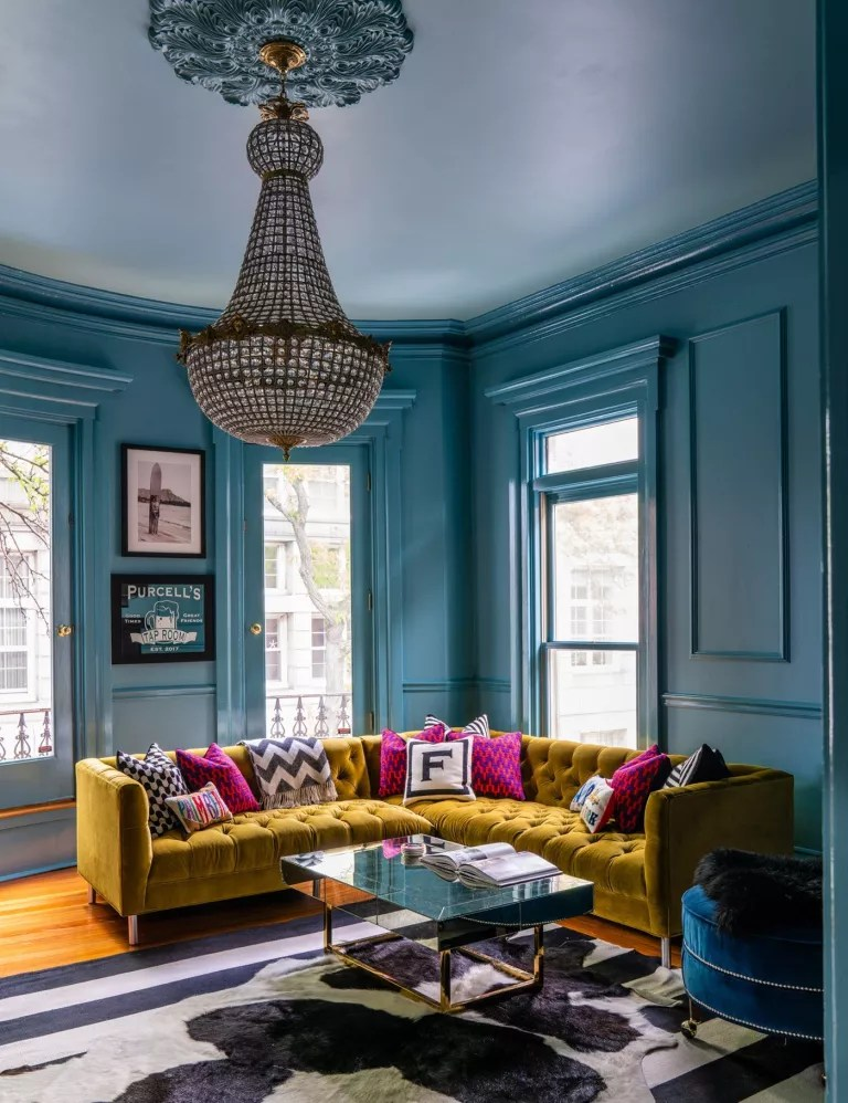 Blue living room with yellow sofa and pink cushions
