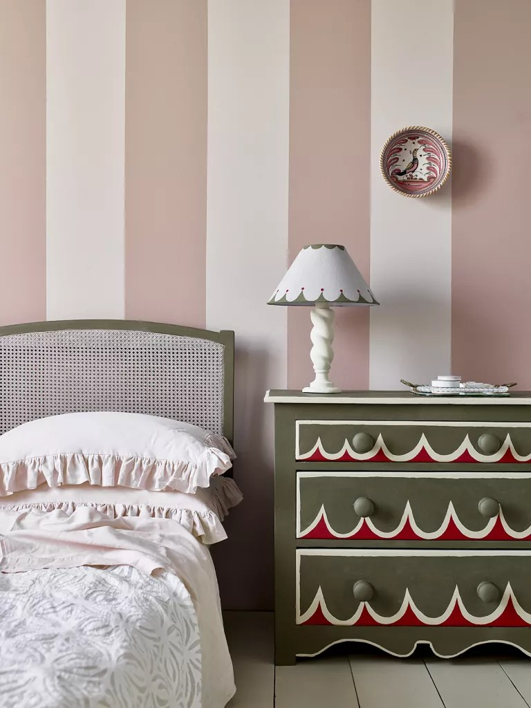 pink and white stripe painted wall with sage green headboard and chest of drawers