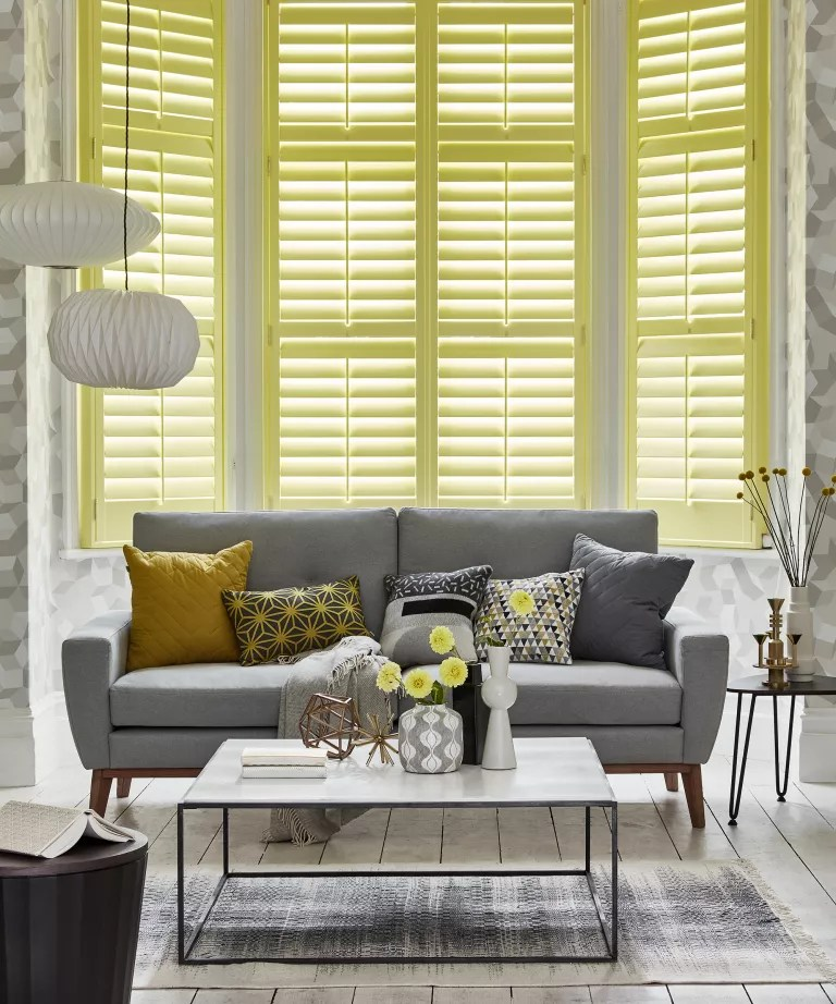 A living room with yellow shutters and a gray sofa
