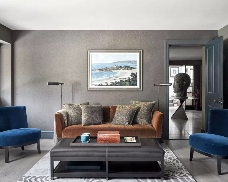 Grey living room with brown sofa and blue chairs