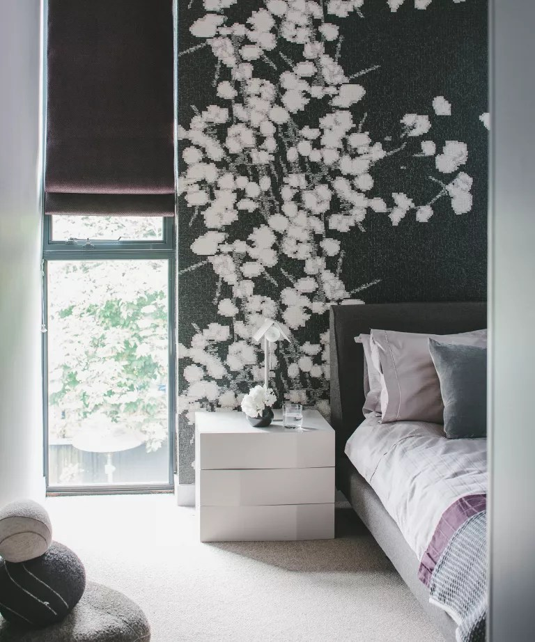 A bedroom with a floor to ceiling window next to a black and white floral wall mural