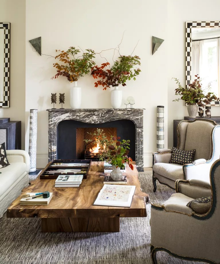 Fall mantel ideas with white walls, grey marble mantel and autumnal leaves in vases
