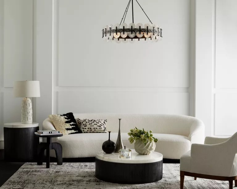 A whiteliving room with white sofa, black coffee table and black chandelier