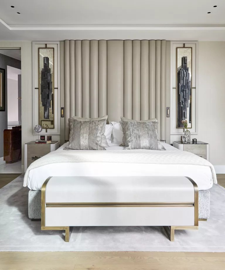 A neutral bedroom with statement headboard and wall sculptures either side of the bed