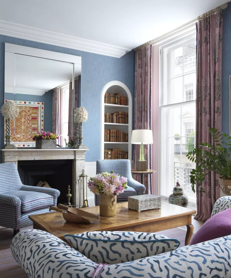A living room curtain idea with blue walls and pale pink patterned curtains