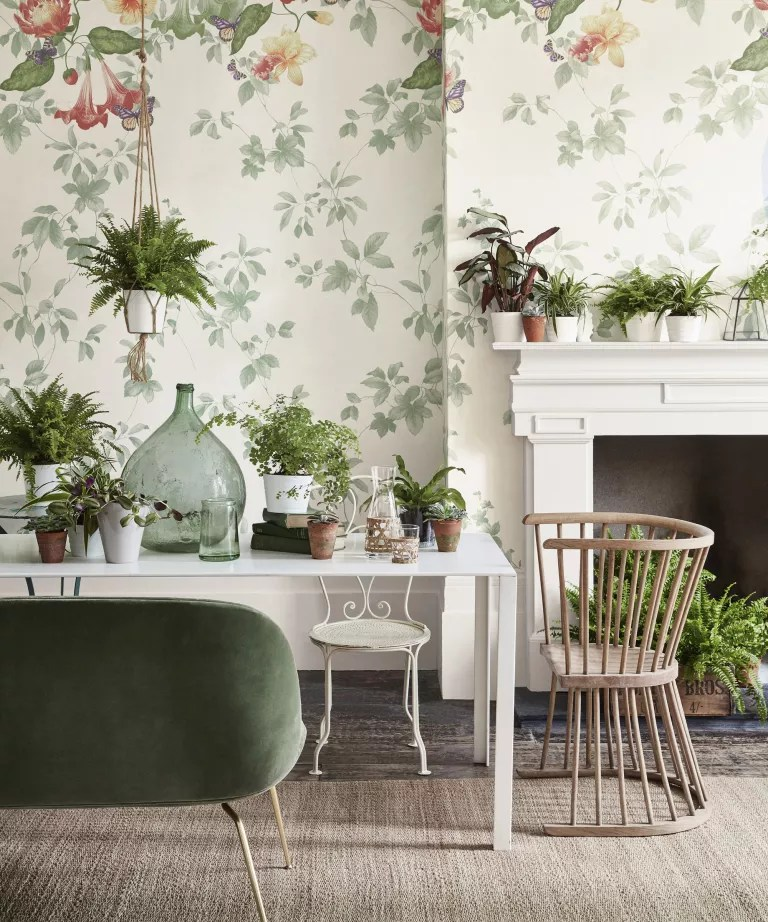 Fall mantel ideas with green plants in white pots on white mantelpiece with green and white nature-inspired wallpaper