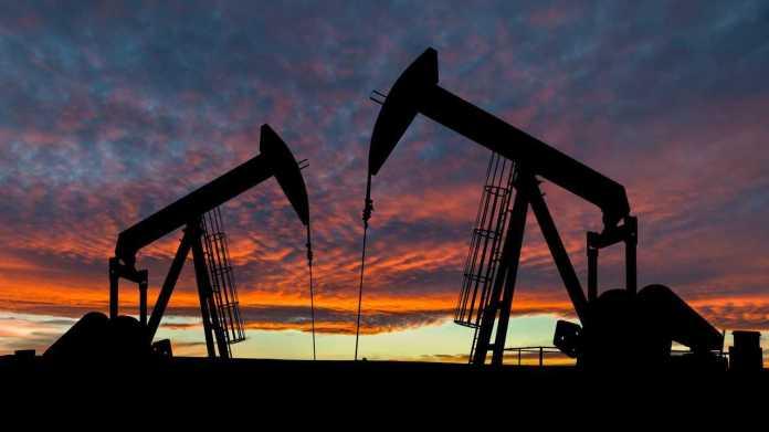 Dramatic sky over two oil pumpjacks in rural Alberta Canada