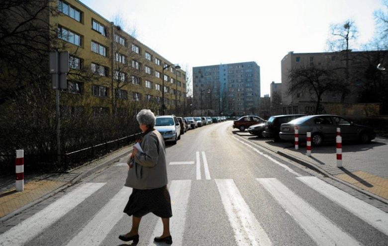 Starsza pani przechodzi przez jedną z warszawskich ulic