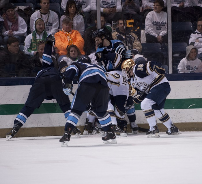 Irish senior forwards T.J. Tynan and Bryan Rust fight for the puck along the boards during  a 2-1 loss to Maine last Friday.