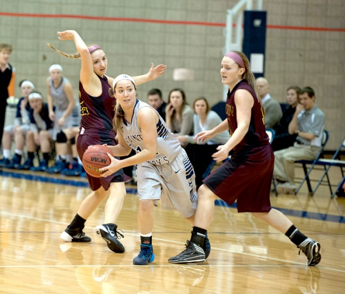 Saint Mary's freshman point guard Kristen Kleist looks to pass while avoiding two defenders during 95-68 loss to Calvin on Jan. 15.