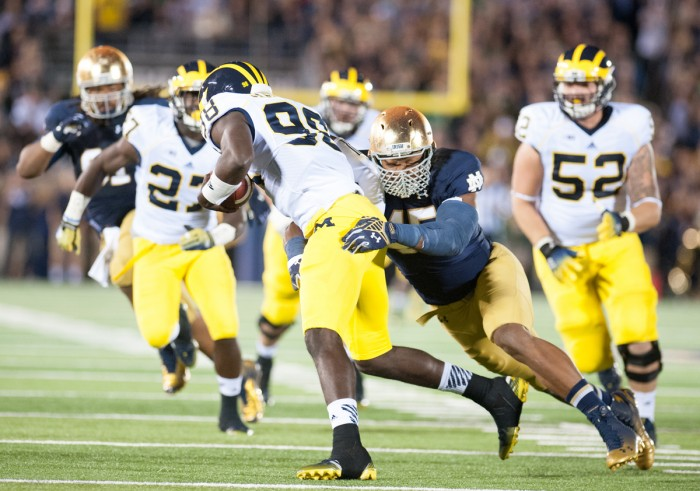 Irish junior defensive end Romeo Okwara tries to bring down Michigan graduate student quarterback Devin Gardner during Notre Dame's 31-0 win over the Wolverines on Saturday at Notre Dame Stadium.