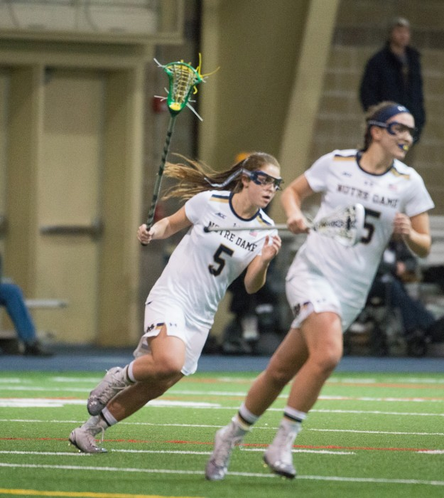 Irish attackers junior Rachel Sexton, left, and sophomore Cortney Fortunato sprint downfield Feb. 15 during a win over Detroit. Both players tallied five goals yesterday in an 18-8 victory over Marquette.