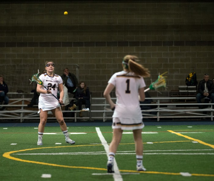 Irish sophomore Casey Pearsall, left, catches a pass from junior Kiera McMullan during a 17-5 win over Detroit Feb. 15.