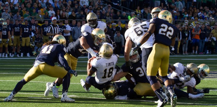 Graduate student cornerback Matthias Farley, 41, and senior safety Elijah Shumate, 22, get in on a tackle during Notre Dame's 41-24 win over Navy last Saturday at Notre Dame Stadium.