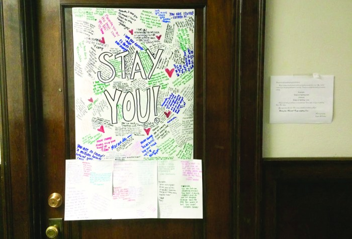 College students write messages of support combatting a hateful message written on Maranda Pennington's white board.