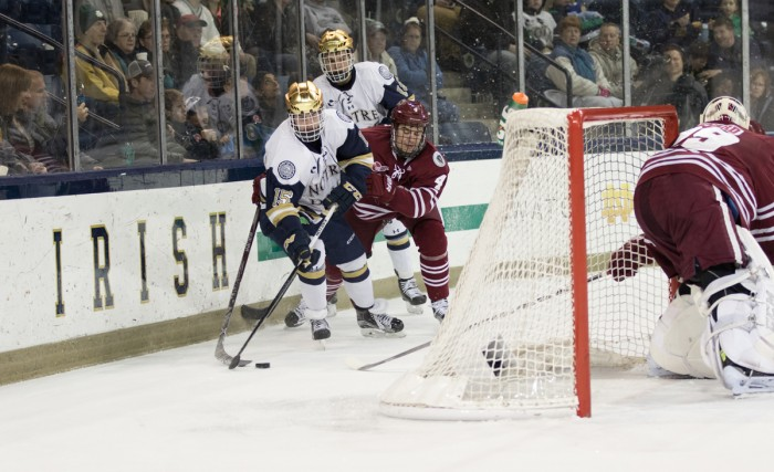 Centers  Andrew Oglevie and Jake Evans fight for the puck during Notre Dame's 5-1 victory over Massachusetts on Sunday.