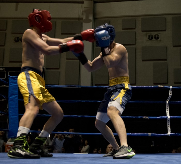 "Senior Liam ""Trooper"" Chan, gold, lands a shot to the head of graduate student Qinfeng Wu during Bengal Bouts action Sunday at the JACC."