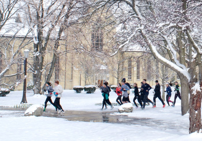 Students and community members run through campus after the Holy Half Marathon was cancelled due to unforeseen icy conditions.