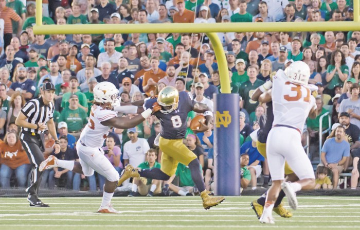 Irish senior quarterback Malik Zaire stiff arms a defender during Notre Dame's 38-3 win over Texas on Sept. 5 at Notre Dame Stadium. Zaire threw for 313 yards in the Irish rout.