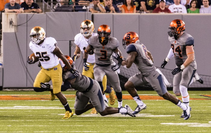 Senior running back Tarean Folston, then a sophomore, attempts to evade a tackler during Notre Dame's 31-15 victory over Syracuse at the Carrier Dome on Sept. 27, 2014.