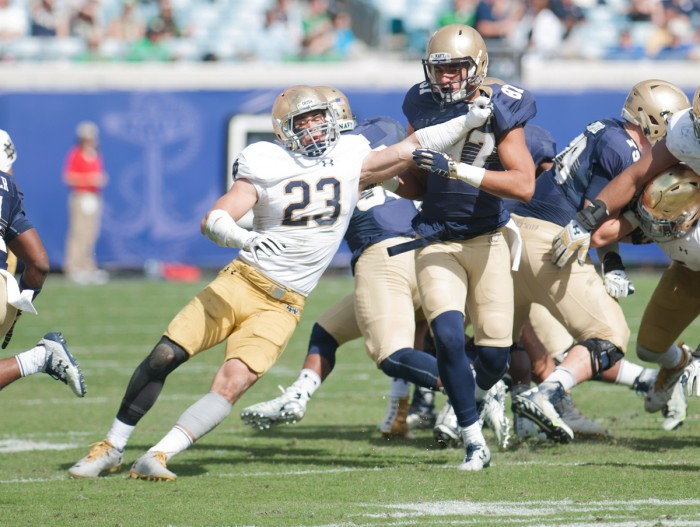 Irish junior safety Drue Tranquill fights through a block during Notre Dame's 28-27 loss to Navy on Saturday at EverBank Field.