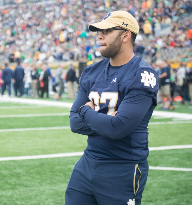 Irish senior receiver Omar Hunter, still recovering from a torn ACL, takes in warm ups in street clothes before the Irish took on Miami.