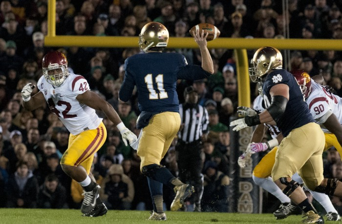 Former Irish quarterback Tommy Rees rolls out to pass during Notre Dame's 14-10 win over USC on Oct. 19, 2013, at Notre Dame Stadium.