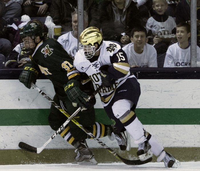 Irish sophomore forward Andrew Oglevie battles with a Vermont player along the boards during Notre Dame's 4-4 draw with the Catamounts on Friday at Compton Family Ice Arena.