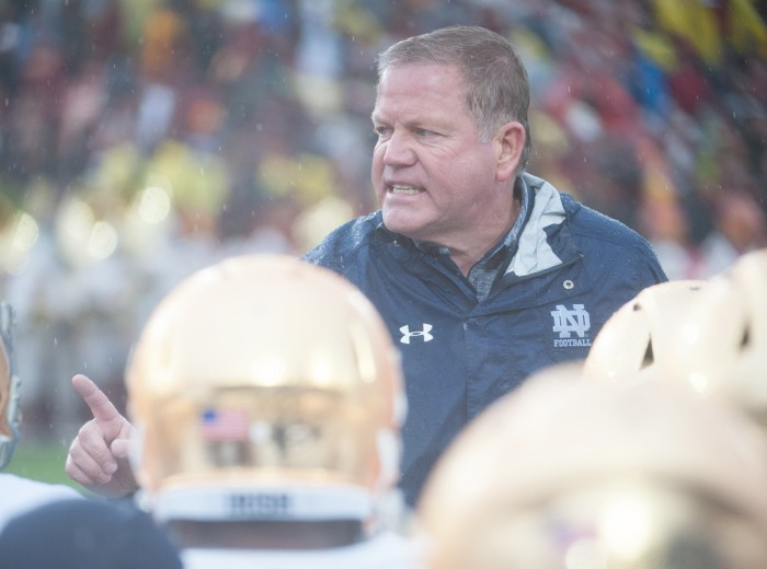 Irish head coach Brian Kelly addresses his team on the field during halftime of Notre Dame's 45-27 loss against USC in Los Angeles on Nov. 26 at the Los Angeles Memorial Coliseum.