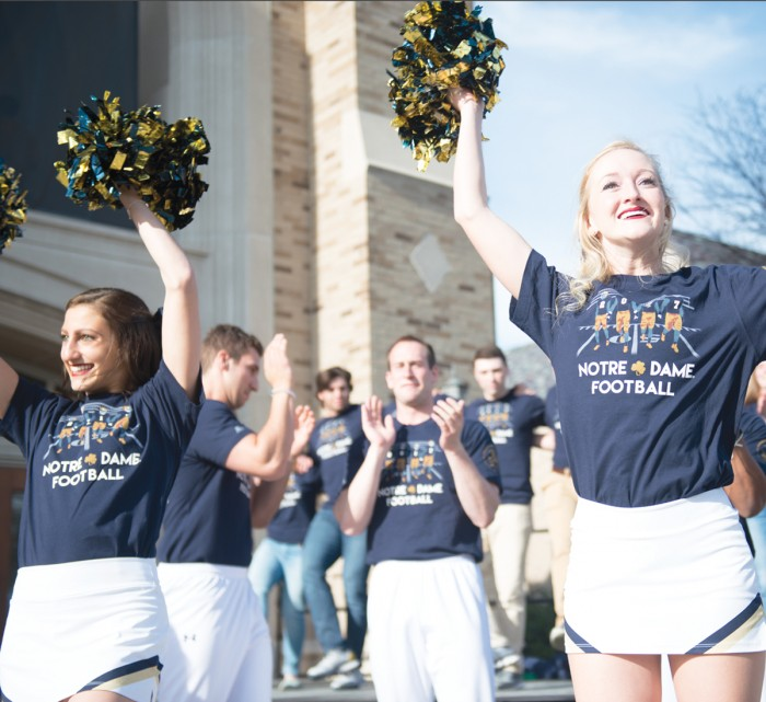 Members of the Notre Dame cheerleading team don the 2017 edition of the shirt as they cheer at the unveiling ceremony at the Hammes Bookstore on Friday.