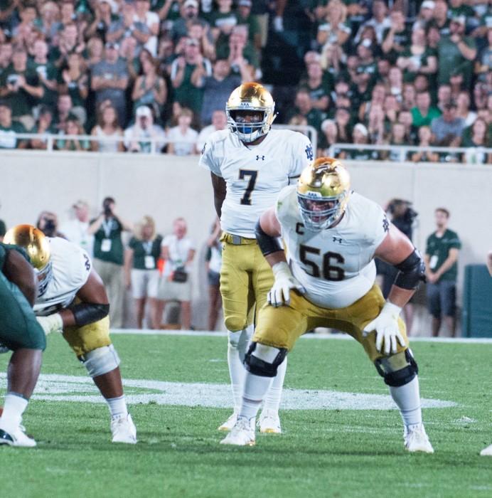 Irish junior quarterback Brandon Wimbush, center, and senior offensive lineman Quenton Nelson prepare for a snap during Notre Dame's 38-18 win over Michigan State on Saturday at Spartan Stadium.