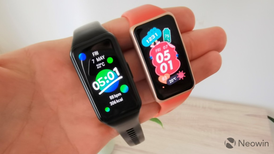 A hand holding a Huawei Band 6 on the right and a Honor Band 6 on the left