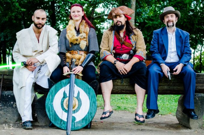Four larpers sit on a bench, one with sword and shield