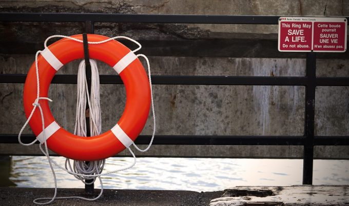 orange life preserver hanging on a wall