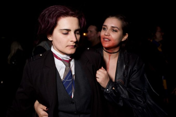 a woman with a bloody face gets the attention of a boy in a tie