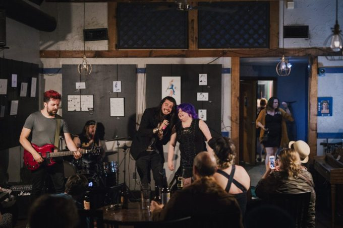 Four band members play in front of a seated audience