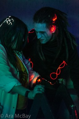 two people with glowing adornments huddle close