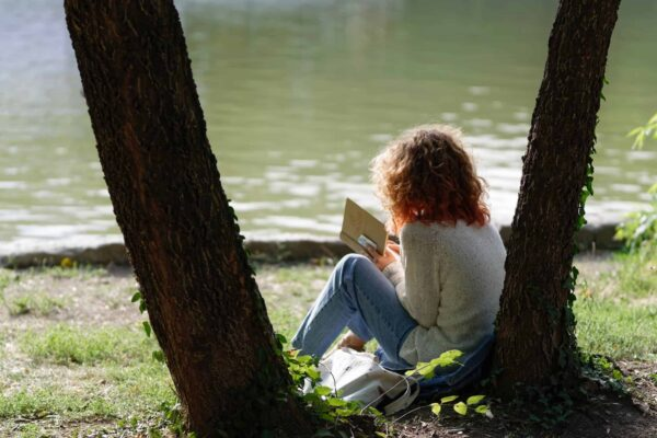 girl with red hair reading a book by a body of water