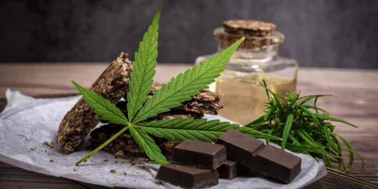 Marijuana leaf and cereal crunchy multigrain chocolate on brown wooden background.