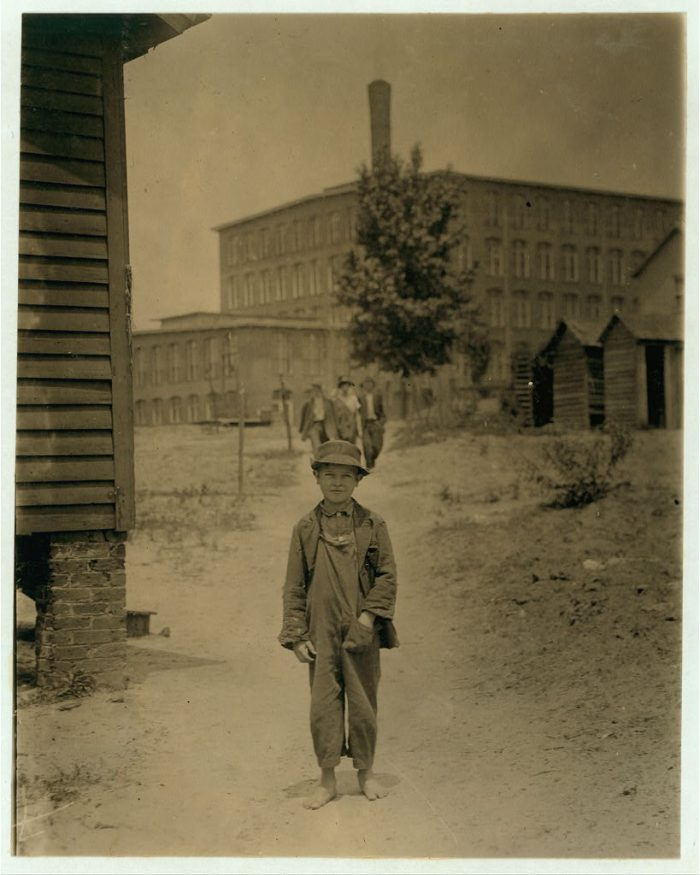 16. This photo taken in May 1912 shows a young boy walking ahead of some adult workers.