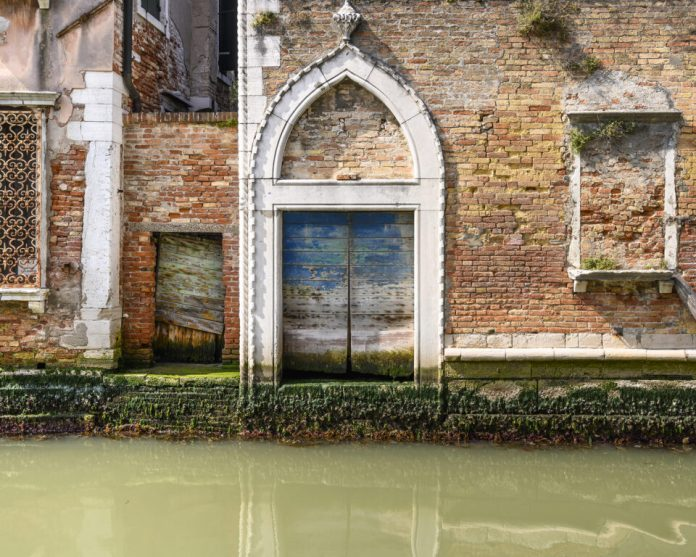 A simple study of beautifully designed and executed architectural detail, set off against ever varied brick work, a visually interesting blue door, much weed and the typical murky green water of a tranquil canal.
